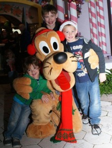 Dominic and his brothers with Pluto at Christmas Give Kids the World Village near Disney World- Toby's Dream Foundation